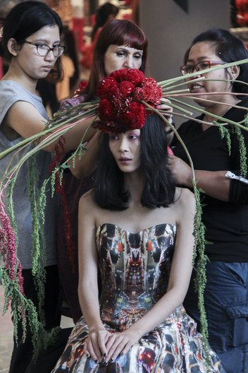 Rebekah Roy making styling adjustments to a handmade floral headpiece Image courtesy British Council Indonesia