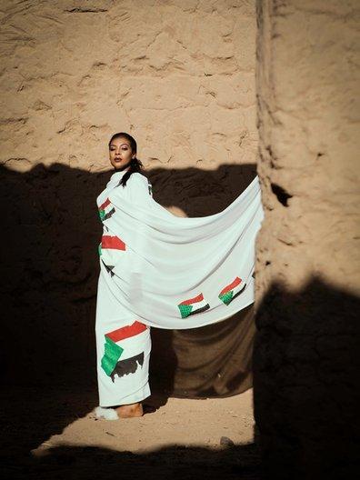 Photographer Maimana Mohammed Abbas  Bona wears Sudan flag toub by Wafaa Basan