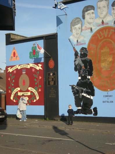 A woman holds her son's toy gun, behind is a UVF mural. Photo Vicky Richardson
