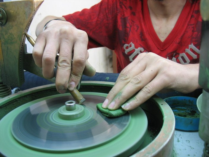 A 3rd year gem-cutting student, Ali, using modern equipment to facet by hand an oval cut gemstone. Photo by Melanie Eddy.