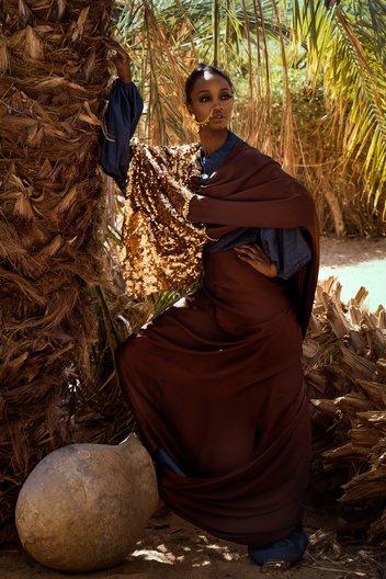 Photographer Maimana Mohammed Abbas Izy wears brown toub by Walaa Khalil and full denim look by Haute Baso